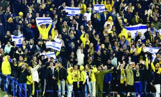Supporters of Beitar Jerusalem cheer for their team during a soccer match against Maccabi Umm el-Fahm at Teddy Stadium in Jerusalem January 29, 2013. Hundreds of police officers and stewards secured the Israeli State Cup match on Tuesday in which Premier League Beitar Jerusalem, supported by a group of vehement anti-Arab fans, host Arab side Maccabi Umm el-Fahm. A racist element among Beitar fans caused uproar in the Jewish state on Saturday when they held up banners during a Premier League match to protest at owner Arkady Gaydamak's planned recruitment of two Chechen Muslim players. REUTERS/Nir Elias (JERUSALEM - Tags: SPORT SOCCER SOCIETY) - RTR3D4PH