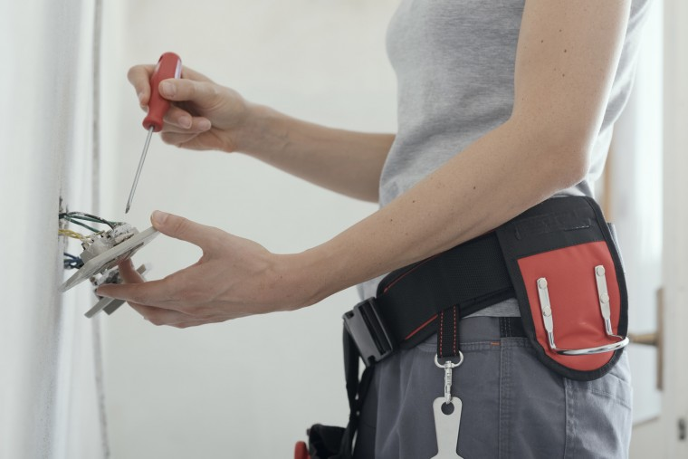 Professional female electrician fixing a socket at home using a screwdriver, home renovation concept