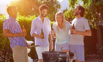 group of friends having outdoor garden barbecue laughing with alcoholic beer drinks
