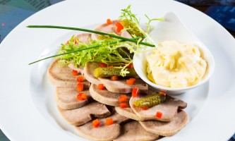 boiled beef tongue sliced on a plate with dill