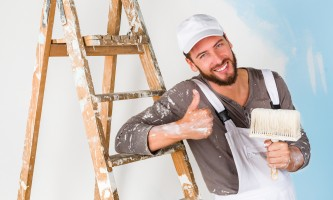 Portrait of handsome young smiling painter in white dungarees, splattered shirt and cap, leaning on a vintage ladder with paint brush, with thumbs up gesture
