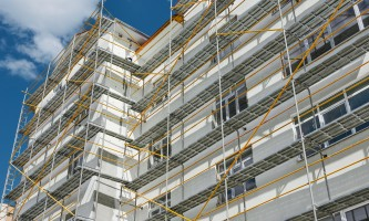 scaffolding near a new house, building exterior, construction and repair industry, white wall and window, yellow pipe