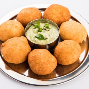 black gram or urad dal vada or pakoda or aalu bonda, aalu bonde with coconut and pudina chutney, isolated