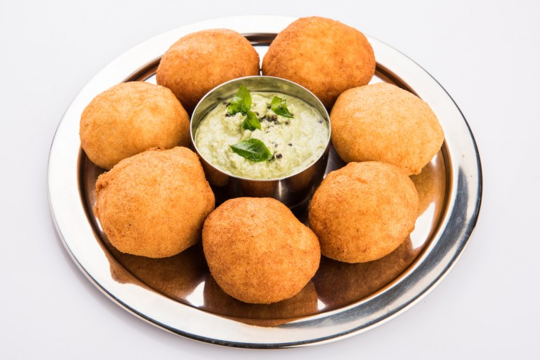 black gram or urad dal vada or pakoda or aalu bonda, aalu bonde with coconut and pudina chutney, isolated