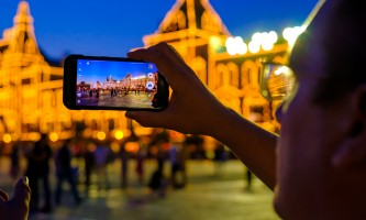 Male tourist taking picture of landmarks by smart phone at night