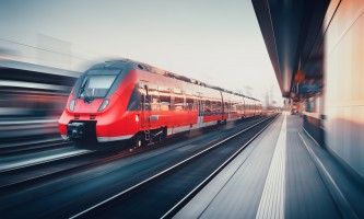 Beautiful railway station with modern high speed red commuter train with motion blur effect at sunset in Nuremberg, Germany. Railroad. Vintage toning. Railroad travel background, tourism. Industrial
