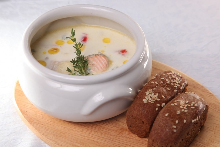 Cream soup with smoked salmon on wooden desk