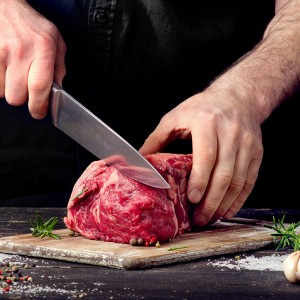 Man cutting raw beef meat.
