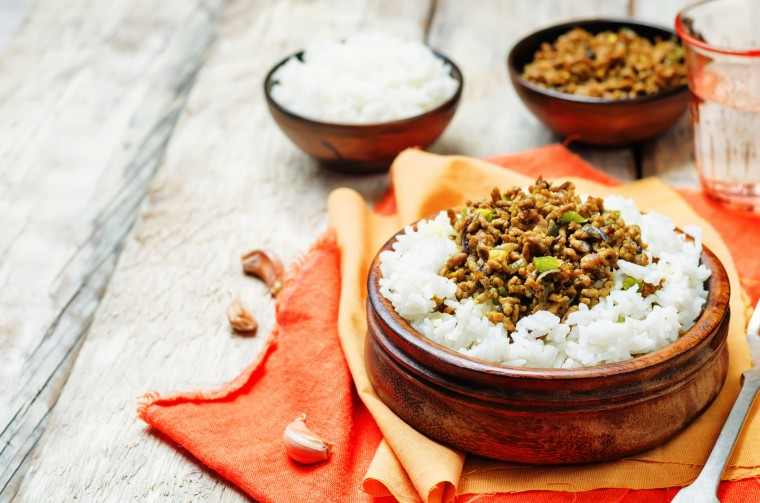 Spicy Indian minced meat with rice on a wood background. toning. selective focus