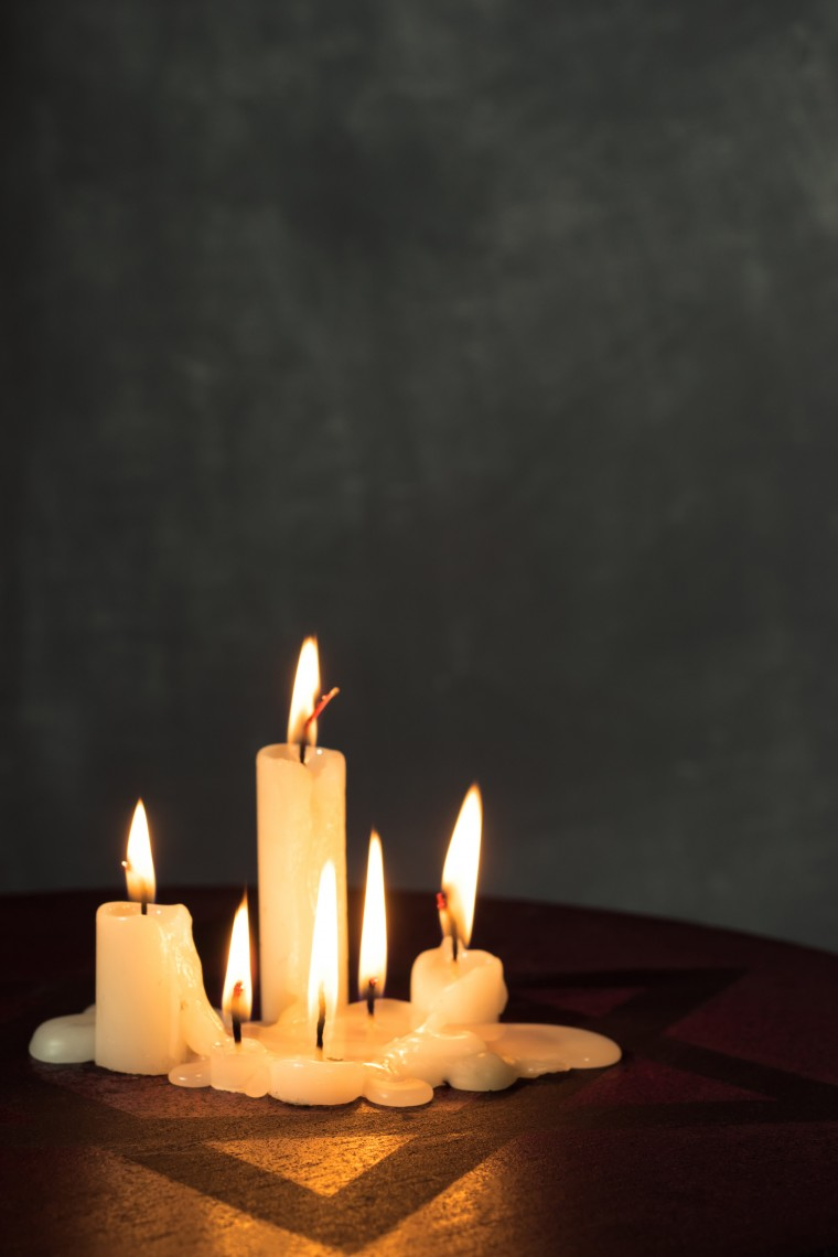 Six burning candles and the Star of David against a dark background.