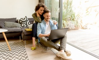 Young couple sitting on floor and using notebook. Online shopping