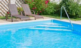 Swimming pool with blue water on a sunny day. Recreation area with a fragment of garden and outdoor furniture.