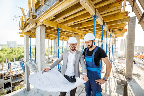 Engineer standing with builder supervising the construction proc