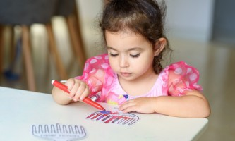 Curly brunette cute little toddler girl painting with color pen